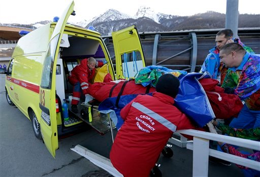 A track worker is loaded into an ambulance after he was injured when a forerunner bobsled hit him just before the start of the men's two-man bobsled training at the 2014 Winter Olympics Feb. 13, 2014, in Krasnaya Polyana. (AP Photo/Charlie Riedel)