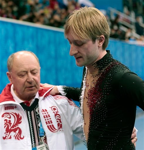 Evgeni Plushenko of Russia, right, and his coach Alexei Mishin leave after Plushenko pulled out of the men's short program figure skating competition due to illness at the Iceberg Skating Palace during the 2014 Winter Olympics.