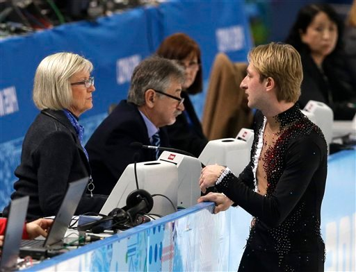 Evgeni Plushenko of Russia speaks with an official prior to pulling out of the men's short program figure skating competition due to illness at the Iceberg Skating Palace during the 2014 Winter Olympics.