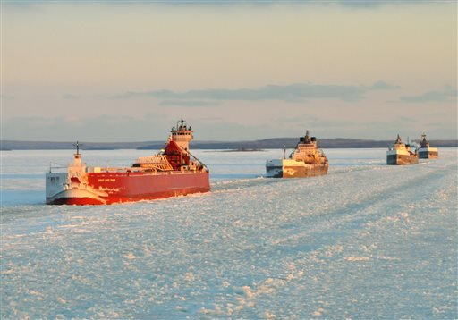 In this Jan. 9, 2014 photo provided by the U.S. Coast Guard a convoy of Great Lakes cargo ships line up to follow an icebreaker on the St. Marys River, which links Lakes Superior and Huron.