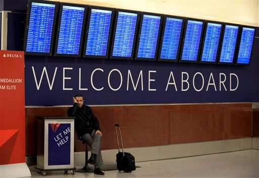 In this Tuesday, Feb. 11, 2014, file photo, Airline passenger Hossam Shalaby, from Egypt, waits for his rescheduled flight to Orlando under the departure board showing hundreds of cancellations at Hartsfield-Jackson International Airport, in Atlanta.