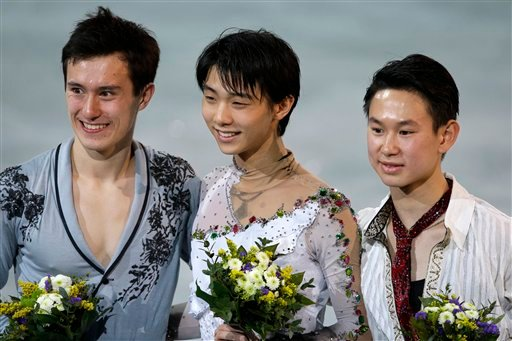 Yuzuru Hanyu of Japan, centre, Patrick Chan of Canada, left, and Denis Ten of Kazakhstan pose for photographs on the podium during the flower ceremony for the men's free skate figure skating final at the Iceberg Skating Palace.