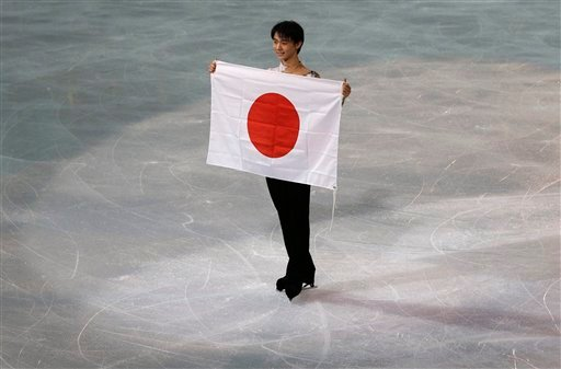 Yuzuru Hanyu of Japan poses with the national flag after he placed first in the men's free skate figure skating final.