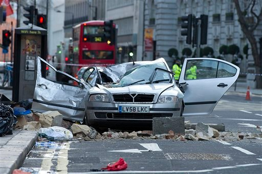 A smashed up car is seen in Kingsway opposite Holborn Tube station in central London, after a woman was killed when large chunks of masonry fell onto a Skoda Octavia vehicle she was in, London, Saturday, Feb. 15, 2014.