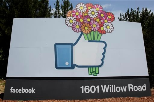 In this Sunday, May 13, 2012, file photo, flowers are added to a Facebook sign in front of Facebook headquarters in Menlo Park, Calif. On Tuesday, Feb. 4, 2014, Facebook celebrates 10 years since its inception. (AP Photo/Paul Sakuma, File)