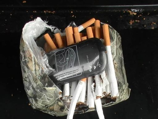This undated photo mprovided by the Florida Department of Corrections shows a cellphone and cigarettes that were found inside a camouflage package, January 25, 2014, near an undisclosed Florida state prison.