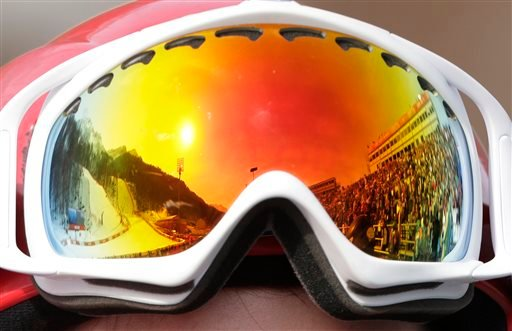 The Alpine ski course is reflected in a skier's goggles during the men's super-G at the Sochi 2014 Winter Olympics, Sunday, Feb. 16, 2014, in Krasnaya Polyana, Russia. (AP Photo/Charlie Riedel)