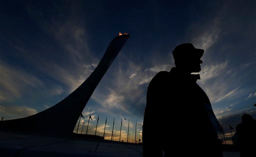 A security team member keeps watch near the Olympic Cauldron as the sun sets at the 2014 Winter Olympics, Friday, Feb. 14, 2014, in Sochi, Russia. (AP Photo/David J. Phillip )