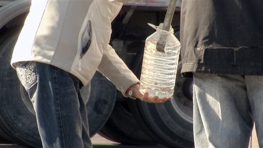 In this Tuesday, Feb. 11, 2014 photo, water brought in by tankers and military vehicles is seen being distributed, in Charleston, W. Va. A chemical leak in the Elk River left residents wary about using tap water.