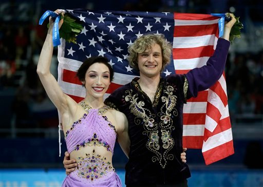 Meryl Davis and Charlie White of the United States pose for photographers with the U.S. flag after placing first in the ice dance free dance figure skating finals at the Iceberg Skating Palace during the 2014 Winter Olympics, Monday, Feb. 17, 2014. (AP)