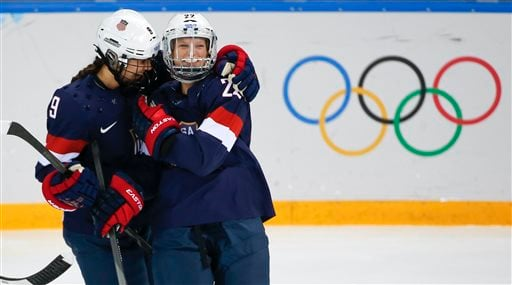 Megan Bozek of the United States, left, congratulates teammate Kacey Bellamy after Bellamy scored a goal against Sweden during the first period of the 2014 Winter Olympics women's semifinal ice hockey game. (AP)