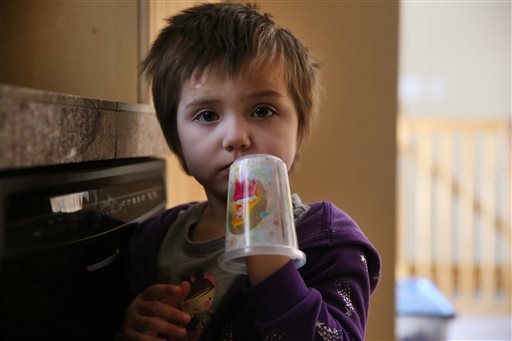 In this Feb. 7, 2014 photo, Elizabeth Burger, 4, plays with a decorative plastic cup at home in Colorado Springs, Colo.