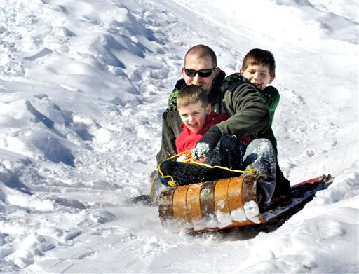 Josh Davis, Bloomsburg, Pa., and his sons Kaden, front, 5, and Cole, 8, ride a toboggan downhill at Josh's cousin Barry J. Davis' home near Bloomsburg, Pa., on Monday, Feb. 17, 2014.