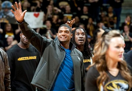 Missouri's All-American defensive end Michael Sam waves to the crowd during the Cotton Bowl trophy presentation at halftime of an NCAA college basketball game between Missouri and Tennessee, Saturday, Feb. 15, 2014, in Columbia, Mo. (AP)