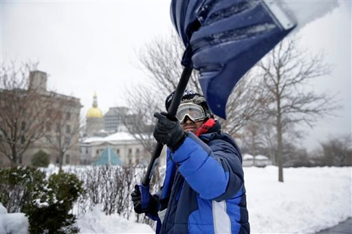 "Marco Garcia, of Guatemala, shovels snow near the Statehouse in Tuesday, Feb. 18, 2014, in Trenton, N.J., after a quick-moving storm brought several inches of snow as well as rare ""thundersnow"" to parts of the winter-weary East Coast. (AP Photo/Mel Evans)"