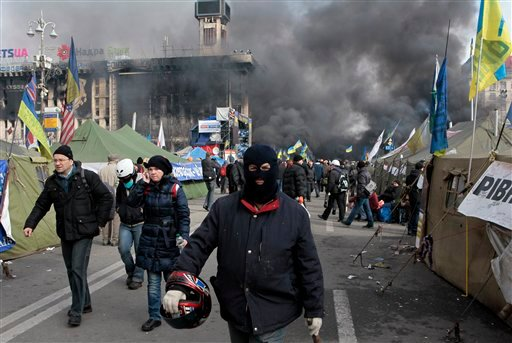 An anti-government protester walks away during clashes with riot police in Kiev's Independence Square, the epicenter of the country's current unrest, Kiev, Ukraine Feb. 19, 2014. (AP Photo/Sergei Chuzavkov)