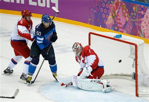 Finland forward Juhamatti Aaltonen (50) scores against Russia defenseman Nikita Nikitin, left, and Russia goaltender Semyon Varlamov in the 1st period of a men's quarterfinal ice hockey game Feb. 19, 2014, in Sochi, Russia. (AP Photo/Mark Humphrey)