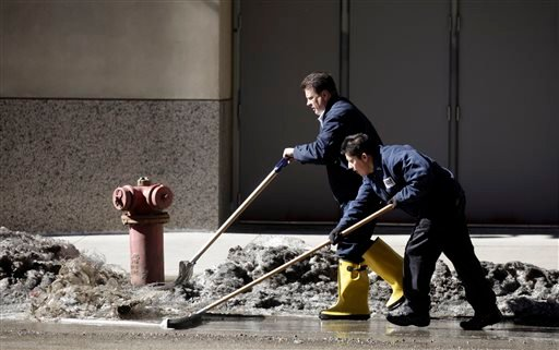 Workers at a downtown parking garage removes snow melt water to the storm drain Wednesday, Feb. 19, 2014, in Chicago. (AP)