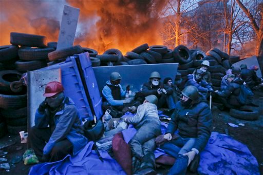 Activists have a rest at the burning barricades, on the side of bloody clashes close to Independence Square, the epicenter of the country's current unrest, Kiev, Ukraine, Thursday, Feb. 20, 2014. (AP)