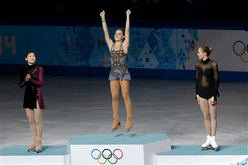 Adelina Sotnikova of Russia, centre, Yuna Kim of South Korea, left, and Carolina Kostner of Italy stand on the podium during the flower ceremony for the women's free skate figure skating final. (AP)