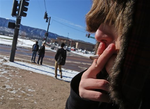 A high school student, who preferred not to be identified, smokes a cigarette in a de facto smoking area just off the property of Lewis-Palmer High School, in Monument, Colo., Thursday Feb. 20, 2014.