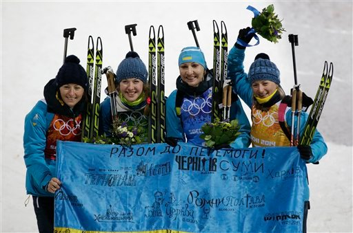 From left, Ukraine's relay team Vita Semerenko, Juliya Dzhyma, Olena Pidhrushna and Valj Semerenko pose with an Ukraine's flag, after winning the gold medal in the women's biathlon 4x6k relay at the 2014 Winter Olympics, Friday, Feb. 21, 2014. (AP)