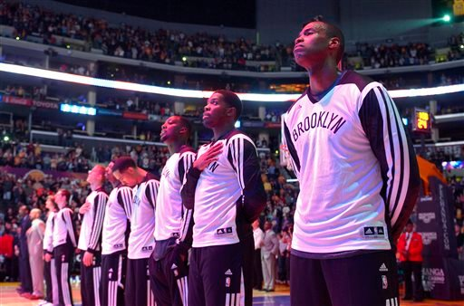 Brooklyn Nets center Jason Collins, right, listens to the national anthem prior to an NBA basketball game against the Los Angeles Lakers, Sunday, Feb. 23, 2014, in Los Angeles. (AP)