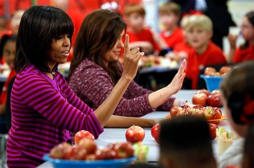 This Feb. 27, 2013 file photo shows first lady Michelle Obama and Food Network chef Rachael Ray discussing lunches with students from the Eastside and Northside Elementary Schools in Clinton, Miss.