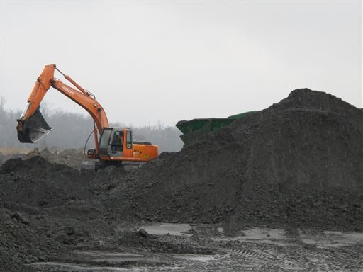 An excavator removes coal ash from the ash pond at Santee Cooper's Jefferies power generating station just outside Moncks Corner, S.C., on Feb. 26, 2014. (AP Photo/Bruce Smith)