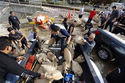 Volunteers fill sandbags in the City of Glendora, Calif., Thursday, Feb. 27, 2014. Residents with the help of their city, prepare for possible flooding. (AP Photo/Damian Dovarganes)