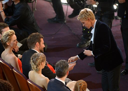 Ellen DeGeneres, right, gives Bradley Cooper a lottery ticket during the Oscars at the Dolby Theatre on Sunday, March 2, 2014, in Los Angeles.