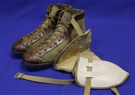 """In this Feb. 19, 2014 photo, a pair of vintage leather and canvas basketball shoes and a set of knee pads are shown as part of an exhibit entitled """"The Black Fives,"""" at the New-York Historical Society in New York."""