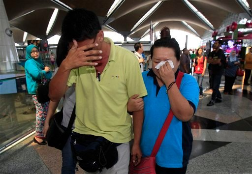 A woman wipes her tears after walking out of the reception center and holding area for family and friend of passengers aboard a missing Malaysia Airlines plane, at Kuala Lumpur International Airport in Sepang, outside Kuala Lumpur, Malaysia.