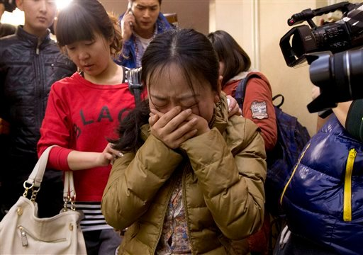 A Chinese relative of passengers aboard a missing Malaysia Airlines plane, center, cries as she is escorted by a woman while leaving a hotel room for relatives or friends of passengers aboard the missing airplane, in Beijing, China Sunday, March 9, 2014.