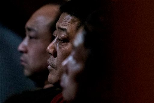 Relatives of Chinese passengers aboard missing Malaysia Airlines Flight MH370 watch a TV news program about the missing flight as they wait for official updates from Malaysia Airlines at a hotel ballroom in Beijing, China, Tuesday, March 11, 2014.
