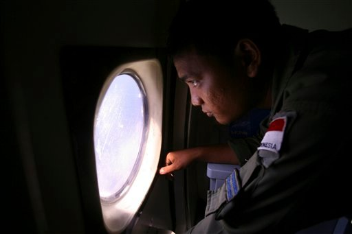 An Indonesian Navy crew member scans the water bordering Indonesia, Malaysia and Thailand during a search operation for the missing Malaysian Airlines Boeing 777 near the Malacca straits on Monday, March 10, 2014. (AP)