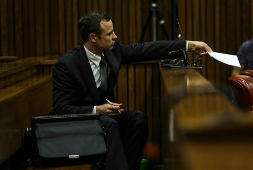 Oscar Pistorius hands a note to his defense team as he listens to cross questioning about the events surrounding the shooting death of his girlfriend Reeva Steenkamp, in court during his trial in Pretoria, South Africa.