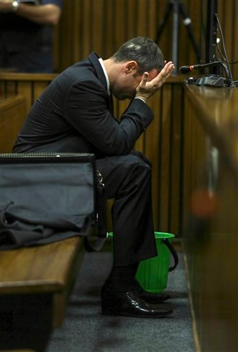 With a bucket on the floor nearby, Oscar Pistorius covers his face with his hands as he listens to cross questioning about the events surrounding the shooting death of his girlfriend Reeva Steenkamp.
