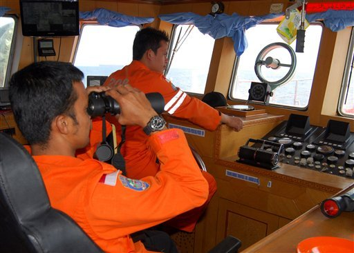 A member of Indonesian National Search And Rescue Agency (BASARNAS) uses a binocular to scan the horizon during a search operation for the missing Malaysia Airlines Boeing 777. (AP)