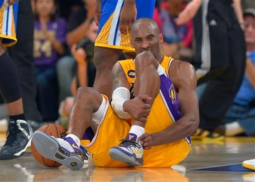 In this April 12, 2013 file photo, Los Angeles Lakers guard Kobe Bryant grimaces after being injured during the second half of their NBA basketball game against the Golden State Warriors, in Los Angeles.