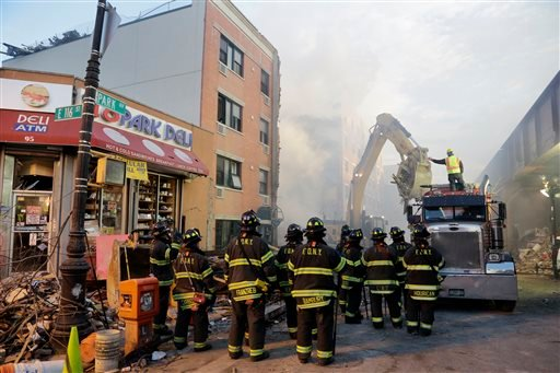 An excavator removes debris from the site of a building explosion, Thursday, March 13, 2014 in New York.