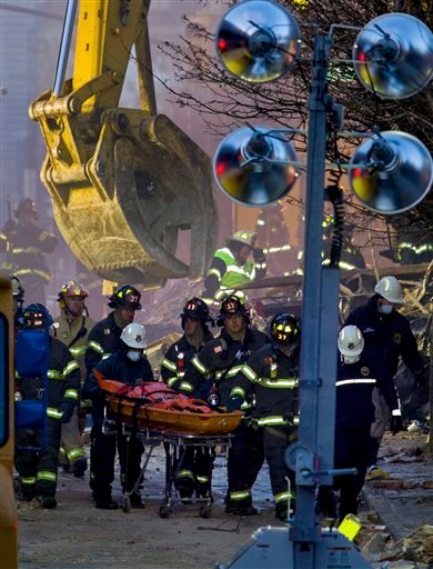 Firefighters remove a body from the scene of the gas explosion in the East Harlem neighborhood of New York, Thursday, March 13, 2014.