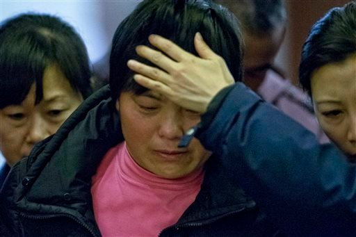 A crying woman, one of the relatives of Chinese passengers aboard missing Malaysia Airlines Flight MH370, is assisted by volunteers as she leaves a hotel ballroom where families were briefed on rescue and searching efforts in Beijing, March 14, 2014.