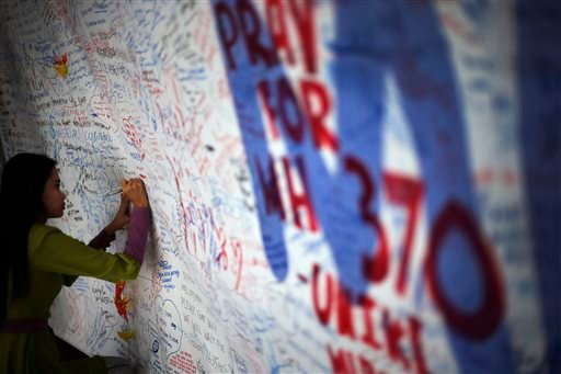 A woman writes on a board of messages and well-wishes dedicated to people involved with the missing Malaysia Airlines jetliner MH370, Saturday, March 15, 2014 in Sepang, Malaysia.