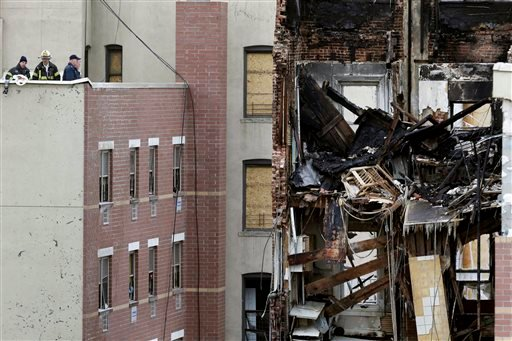 Firefighters look over the site of a building explosion in New York, Friday, March 14, 2014.