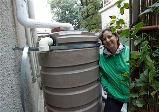 In this Feb. 28, 2014 photo, Santa Monica, Calif., resident Josephine Miller stands next to her 200-gallon water storage tank that collects rain from her home's roof to water her garden.