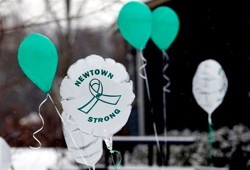 In this Dec. 14, 2013 file photo, Balloons fly outside a doctor's office on the first anniversary of the Sandy Hook massacre, in Newtown, Conn., Saturday, Dec. 14, 2013.