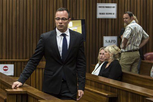 Oscar Pistorius, left, walks past June Steenkamp, back left, mother of Reeva Steenkamp, and Jenny Strydom, as he arrives in court Monday, March 17, 2014 in Pretoria, South Africa.