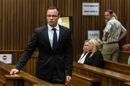 Oscar Pistorius, left, walks past June Steenkamp, back left, mother of Reeva Steenkamp, and Jenny Strydom, as he arrives in court Monday, March 17, 2014 in Pretoria, South Africa.