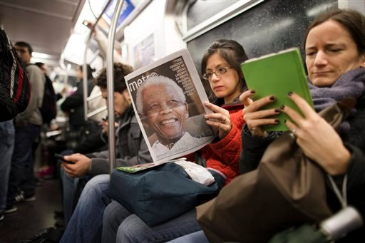FILE - In this Dec. 6, 2013, file photo, a subway rider in New York reads a newspaper featuring news of the death of South African leader Nelson Mandela. (AP)
